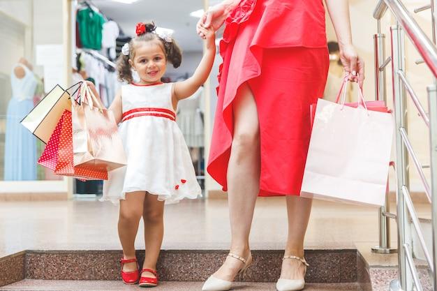 Mamá con hija pequeña en vestidos en el centro comercial con bolsas de colores