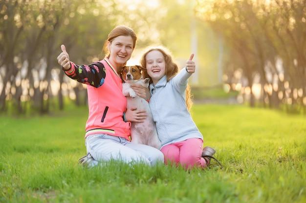 Mamá con la hija y el perro muestran el pulgar hacia arriba en el parque de la primavera.