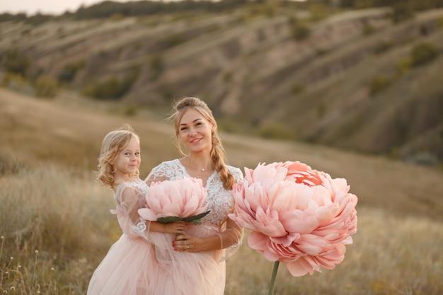 Mamá con hija en vestidos de cuento de rosa camina en la naturaleza