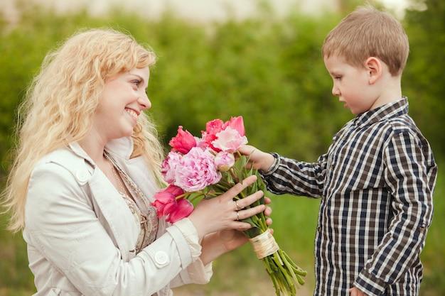 Mamá con hijo y flores para el día de la madre.