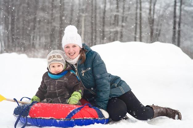 Mamá hijo montar en un tubo inflable de trineo de invierno
