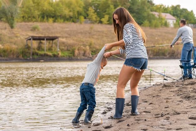 Mamá con un hijo pequeño camina por la orilla arenosa del lago con botas de goma. salir con niños en la naturaleza, lejos de la ciudad.