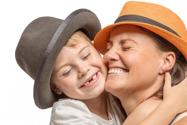 Mamá con un hijo pequeño en sombreros abrazándose y riéndose, linda familia