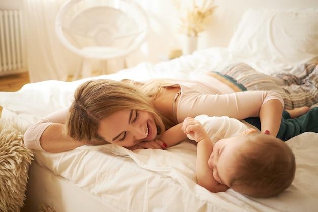 Mamá joven encantadora en traje de noche holgazaneando en la cama junto con su lindo bebé, hablando entre sí después de despertar, con expresión facial feliz. vínculos familiares, concepto de maternidad e infancia