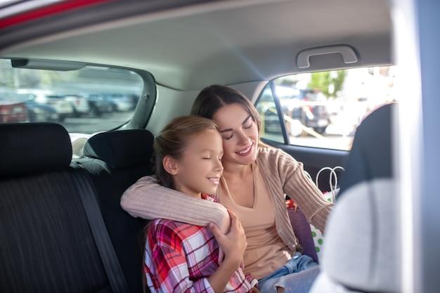 Mamá joven feliz abrazando a su hija, sentada mejilla con mejilla en el asiento trasero del coche