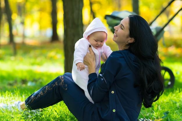 Mamá joven feliz jugando con una linda niña en el césped de un parque en otoño