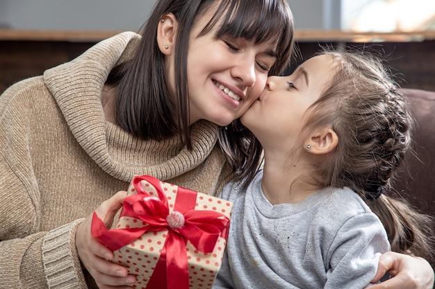 Mamá joven feliz con su linda hija. el concepto de felicitaciones por las vacaciones, las relaciones familiares y el tiempo de calidad juntos.