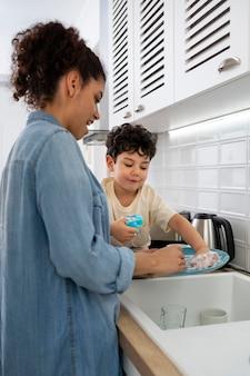 Mamá joven lavando platos con su hijo