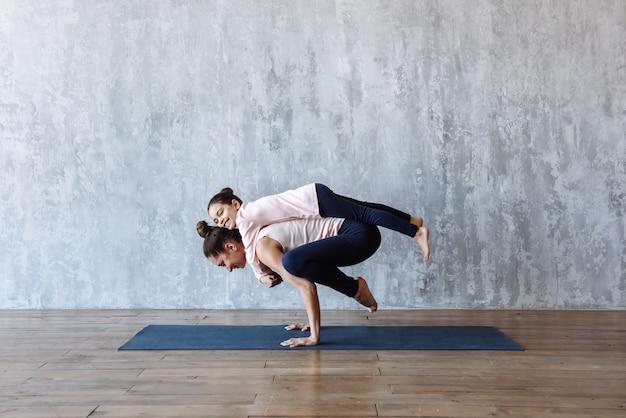 Mamá joven y linda hijita juegan juntas y practican yoga deportivo en la colchoneta