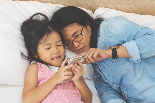Mamá joven y su pequeña hija están usando un teléfono inteligente en la cama en casa