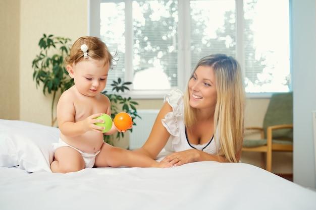 Mamá juega con el bebé en la cama de la habitación.