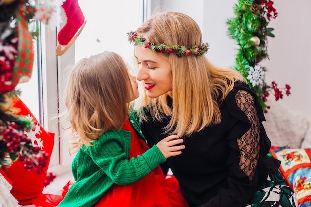 Mamá juega con hija pequeña antes de una ventana brillante decorada para navidad