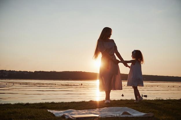 Mamá juega con su bebé de vacaciones cerca del océano, siluetas al atardecer