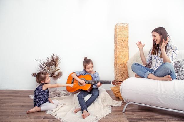 Mamá juega con sus hijas en casa. lecciones de instrumentos musicales
