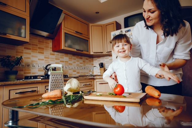 Mamá junto con su hija cocina verduras en casa en la cocina