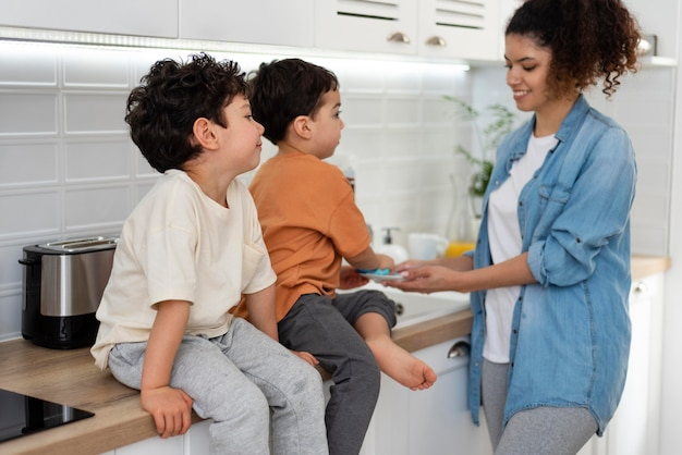 Mamá lavando platos con sus hijos