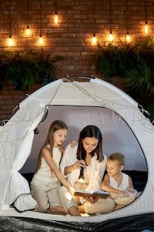 Mamá lee a los niños un cuento antes de dormir sentado en una tienda de campaña en casa. madre hijo e hija se abrazan y leen un libro con una linterna en sus manos