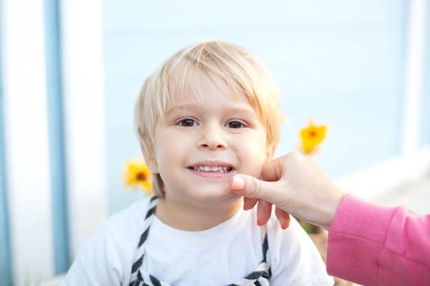 Mamá limpia la cara de un niño pequeño cuidado del bebé sonriente niño rubio niño se ensució