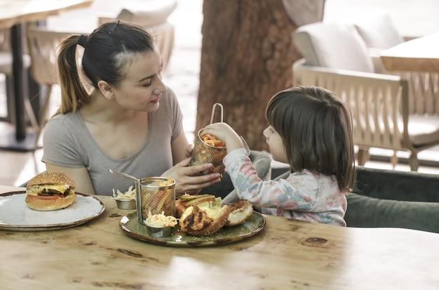 Mamá con una linda hija comiendo comida rápida en un café