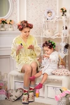 Mamá con una linda hijita pinta sus uñas. día de la belleza de una hermosa madre y su pequeña hija.