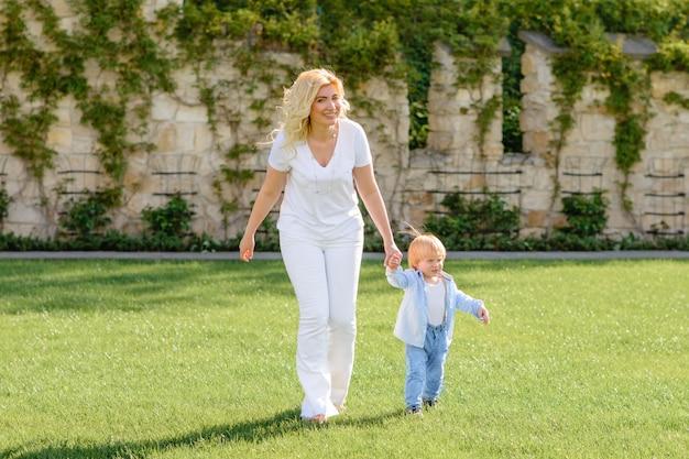 Mamá lleva la mano de su hijo por la hierba verde