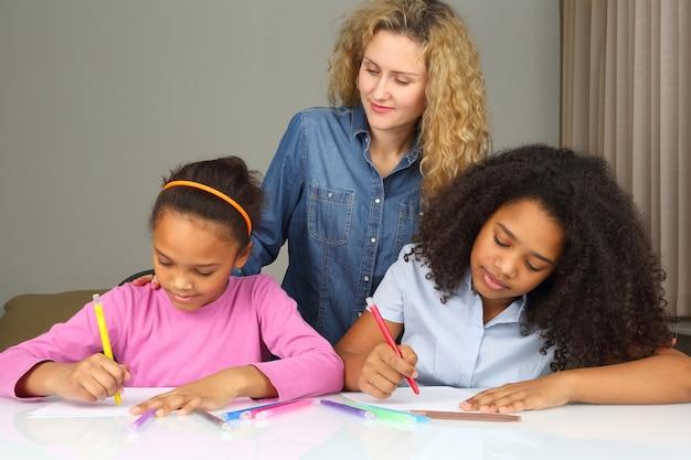 Mamá mira como su hija dibuja con crayones