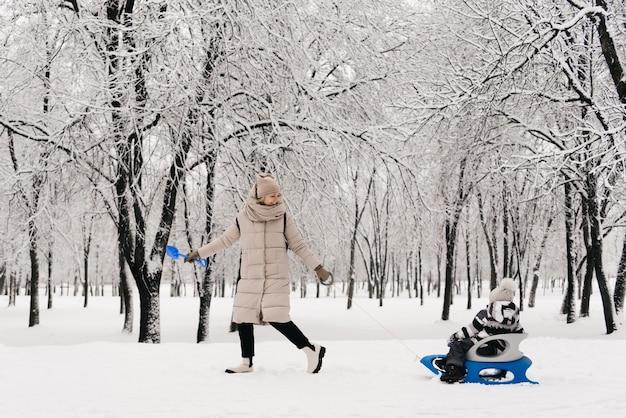 Mamá monta a un chico lindo en un trineo en la nieve, estilo de vida activo, invierno, familia