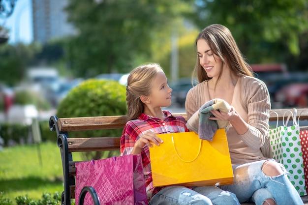 Mamá mostrando a su hija nueva bufanda, sentada en un banco del parque