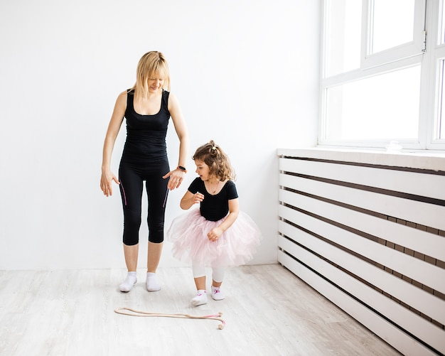 Mamá mujer se entrega a bailar con su pequeña hija, se dedica a la gimnasia en interior blanco