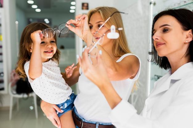 Mamá y niña buscando monturas de gafas