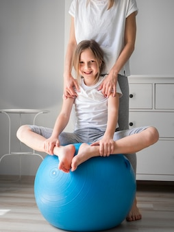 Mamá y niña hacen ejercicio en la pelota juntas