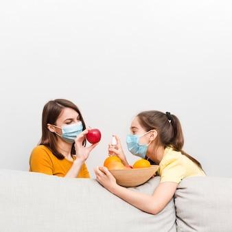 Mamá y niña con máscara y frutas en casa
