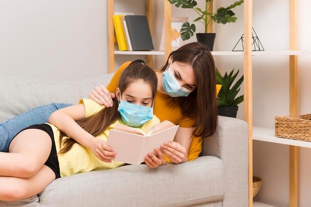 Mamá y niña con máscara de lectura