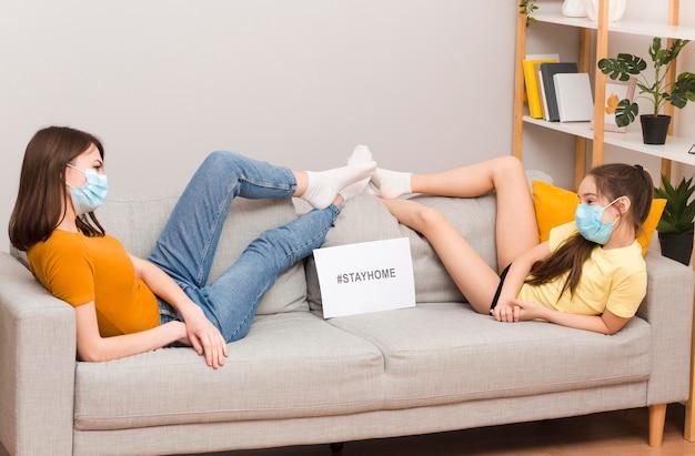 Mamá y niña con máscara en el sofá jugando