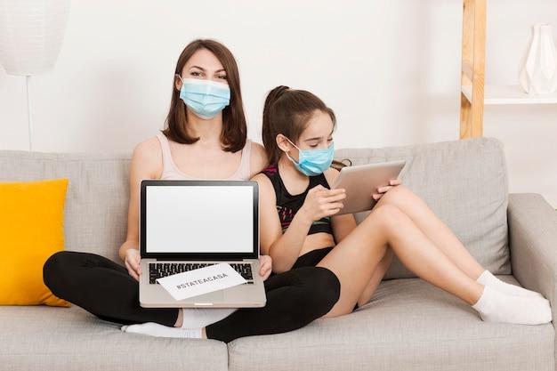 Mamá y niña en el sofá con dispositivo electrónico