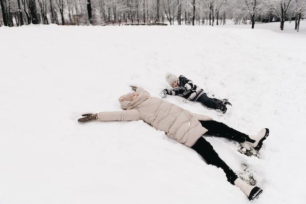 Mamá y niño se divierten en la nieve, estilo de vida activo, invierno, familia