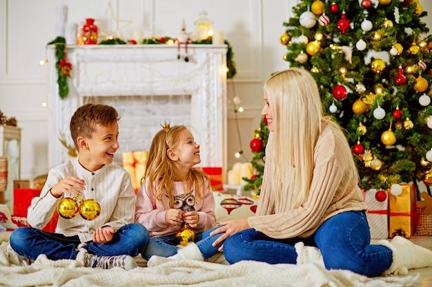 Mamá con niños en el árbol de navidad con regalos, felicítense felizmente.