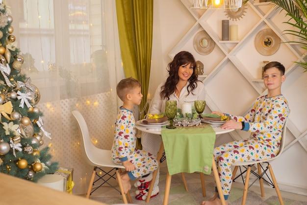 Mamá con niños en la cocina juntos en navidad familia feliz