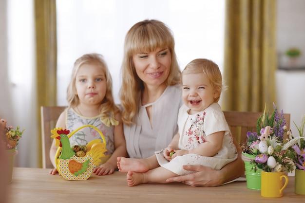 Mamá y niños con coloridos huevos de pascua en la mesa