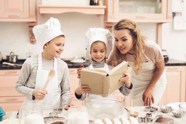 Mamá y niños leen el libro de recetas en la cocina de la casa.
