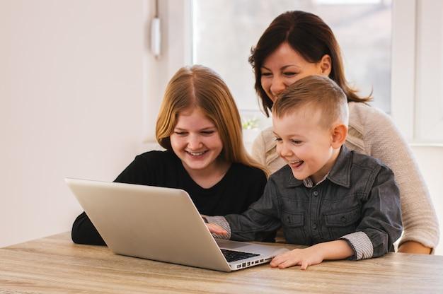 Mamá y niños mirando dibujos animados en la computadora portátil en casa