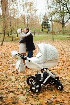 Mamá y papá abrazándose en un parque de otoño