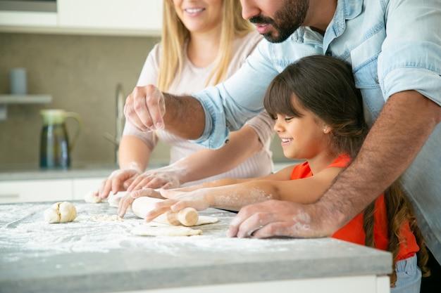 Mamá y papá alegres enseñando a hija feliz a enrollar la masa en la mesa de la cocina con harina desordenada pareja joven y su chica horneando bollos o pasteles juntos. concepto de cocina familiar