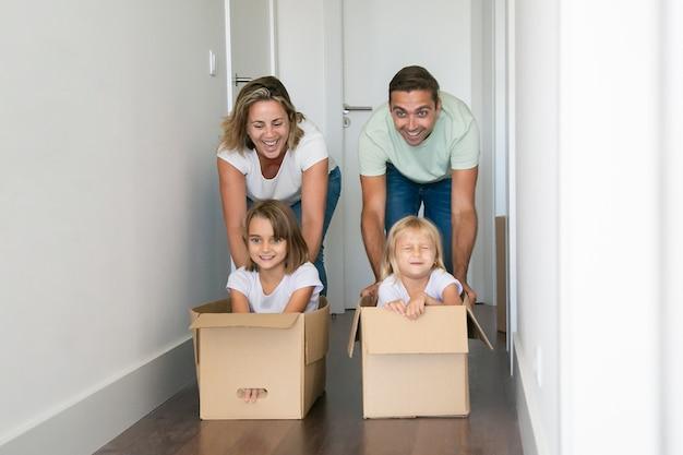 Mamá y papá caucásicos empujando cajas de cartón con niños dentro