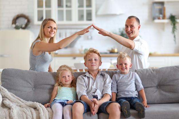 Mamá y papá haciendo figura del techo con las manos brazos sobre tres niños hads. concepto de vivienda.