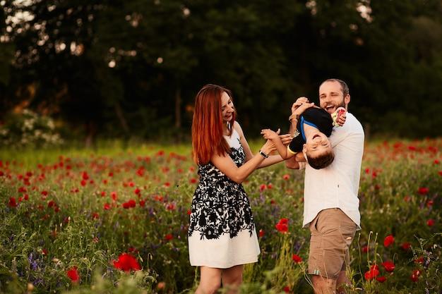 Mamá y papá sostienen a su pequeño hijo en los brazos que se colocan en el campo verde con amapolas
