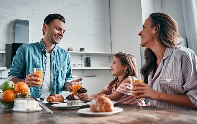 Mamá, papá y su pequeña y hermosa hija desayunan en la cocina y conversan. concepto de familia feliz.