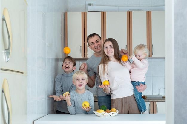 Mamá, papá y tres niños en la cocina sostienen frutas en sus manos y se ríen.