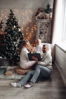 Mamá y papá ven dibujos animados en la computadora portátil con su bebé cerca del árbol de navidad