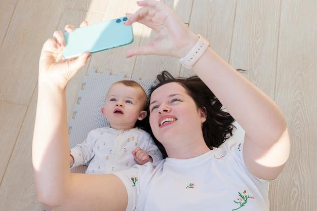 Mamá pasando tiempo con su hijo bebé tomando una selfie con un teléfono